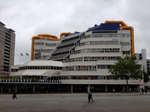 "The Central Library was completed in 1981 and designed by Rotterdam Architect Bakema.  ""The building is shaped like a cube with a cut off corner, a glass 'waterfall' where the escalators are located that connect the six floors"" (Architecture in Rotterdam)."