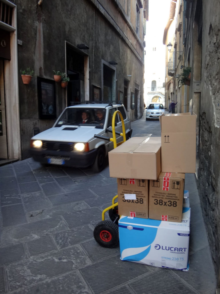 Traffic continues on the narrow streets of Todi even as goods are unloaded for local shops. Todi, Italy 2016