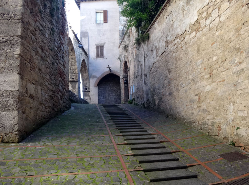 A side street with tiny steps to climb and long, smooth tracks for water to flow downhill. Todi, Italy 2016.