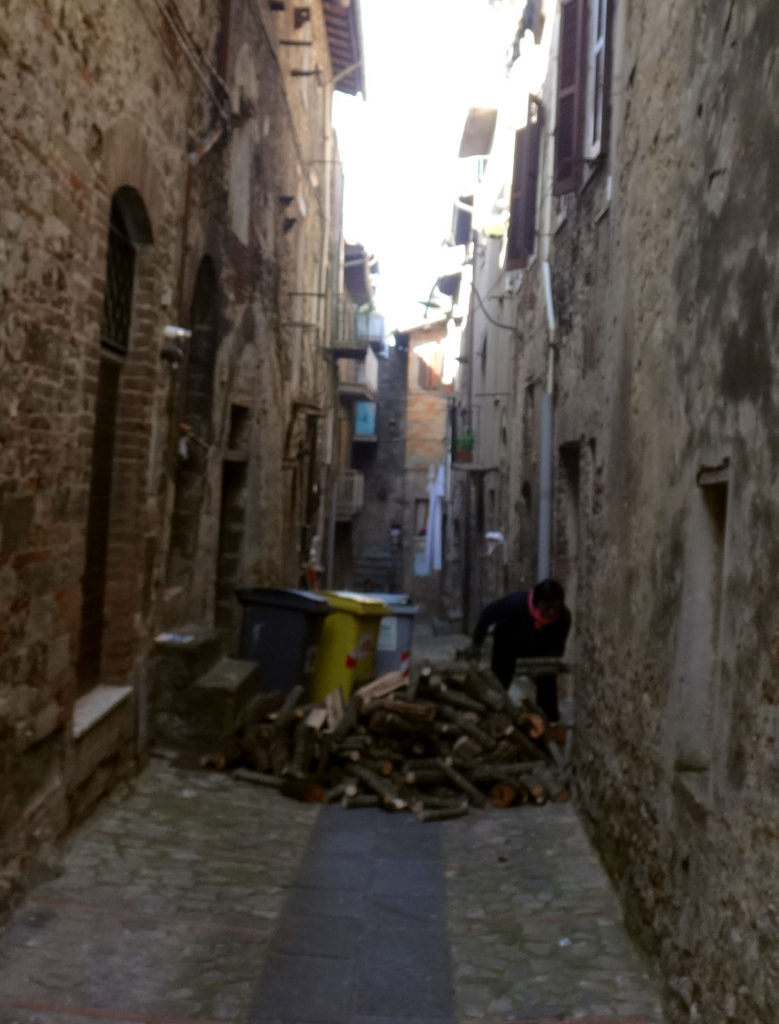 A resident brings in firewood from an alley in Todi, Italy 2016.