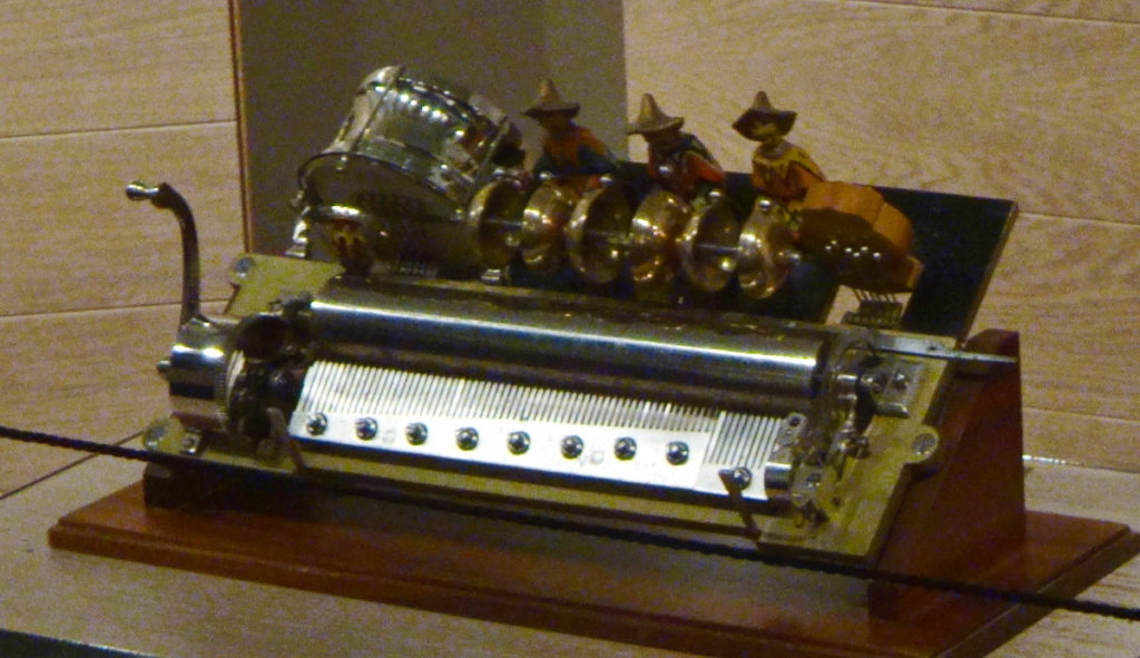 When you turn the handle on this little automaton, the spindles play music and the band members at the top play drums.